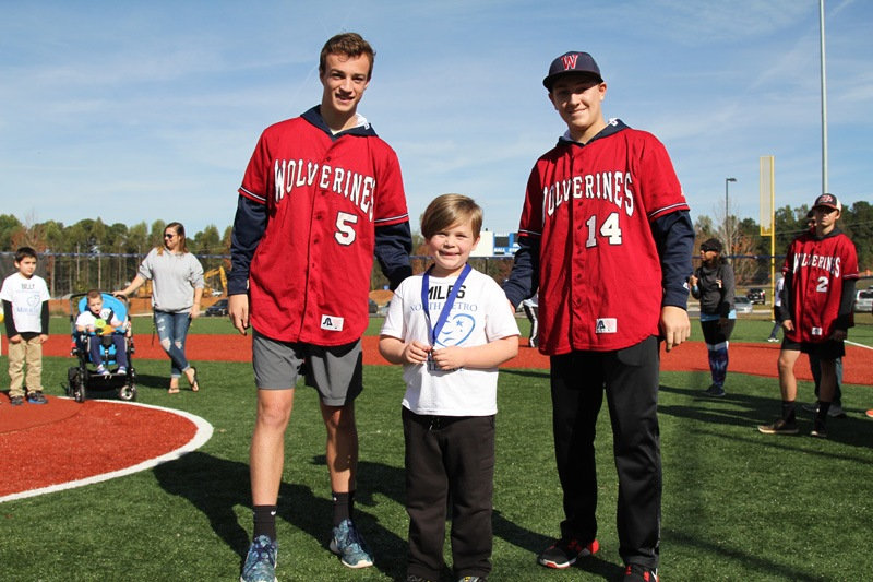 Woodstock players assist with the North Metro Miracle League