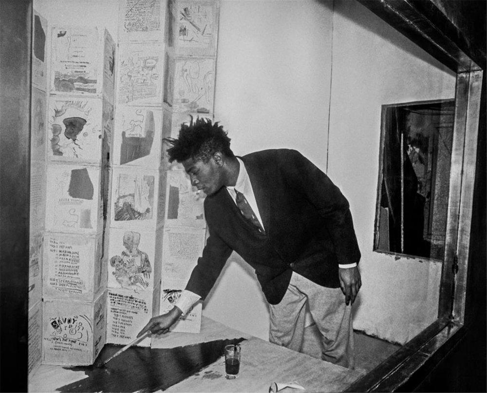 Basquiat retocando uma vitrine com obras em 1985