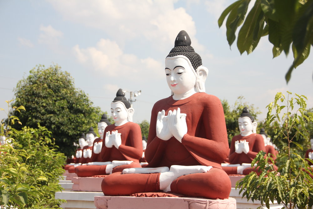 Several colorful buddha statues surrounded by trees