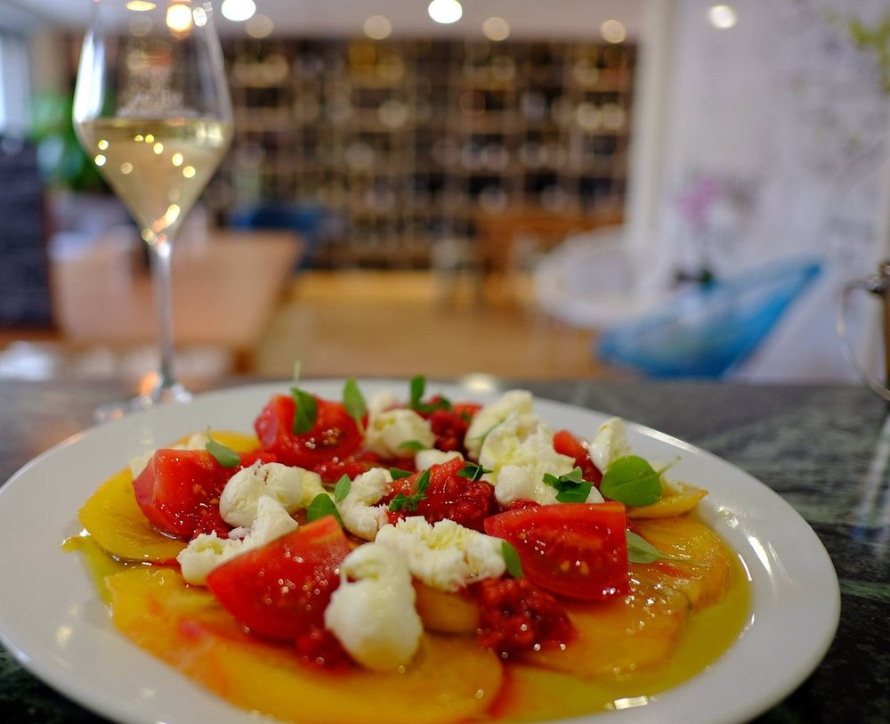 Salade de tomates anciennes, mozzarella, framboises et basilic