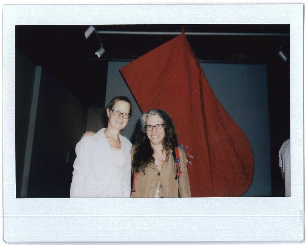 Artists Judith Schaechter and Astrid Bowlby standing before Bowlby's giant red mitten at Arcadia University Art Gallery