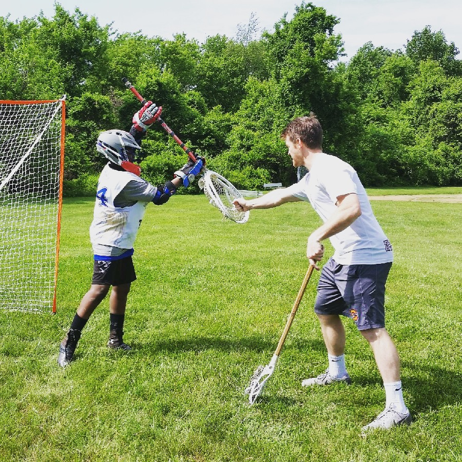 Owner/UPenn Coach Dave Page works with a first-time goalie from Harlem Lacrosse giving the position a shot!