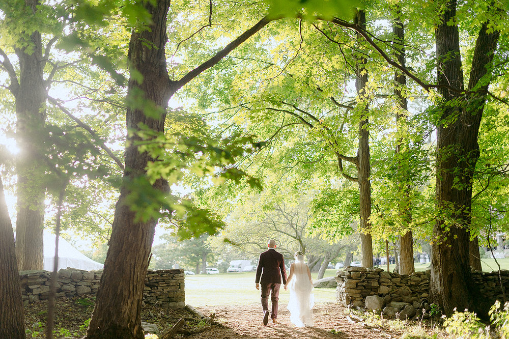 Sun filtering through the trees as bride and groom walk away at the Carey Institute for Global Good
