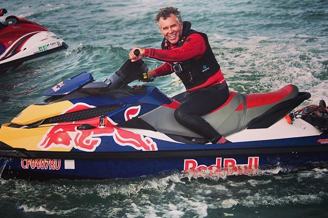 Surfer Jeff Clark stepping off the board and onto a jet ski #jeffclark #jetski #ocean #waves #beach #beachlife #openwater #rashguard #lifejacket #fast #horsepower #surfer
