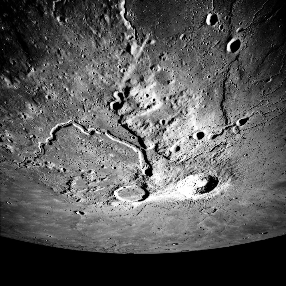 (Left) Apollo 15 Mapping Camera image (A15-M-2610) of the Aristarchus plateau. Note the large, fresh Aristarchus crater, as well as the sinuous rille Vallis Schroteri. The entire uplifted, hummocky plateau has been mantled by pyroclastic materials. (Right) Topography of the Cobra Head region of the plateau. All of the major volcanic features on the plateau (Cobra Head, Vallis Schroteri, the pyroclastic deposit, and the irregular cones) may have been formed from an eruptive vent located at Cobra Head.
