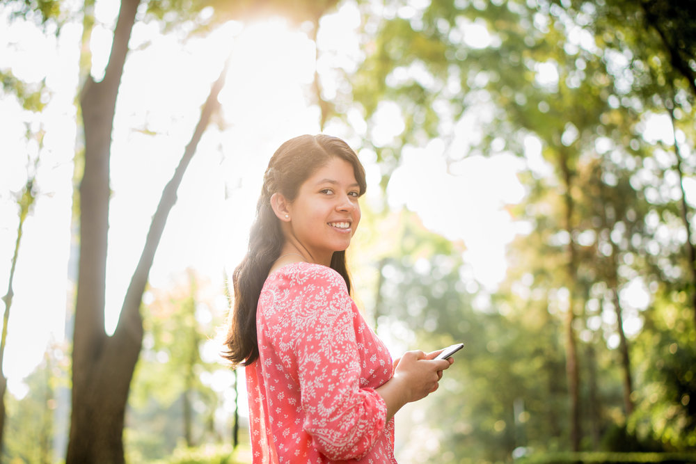 Latin girl holding mobile and smiling at camera_iStock_XXXLARGE_purchased 2016-11-16.jpg