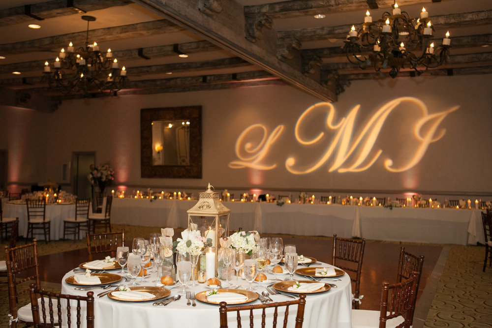 Gobo with the bride and groom's initials taking up the wall behind the bridal table