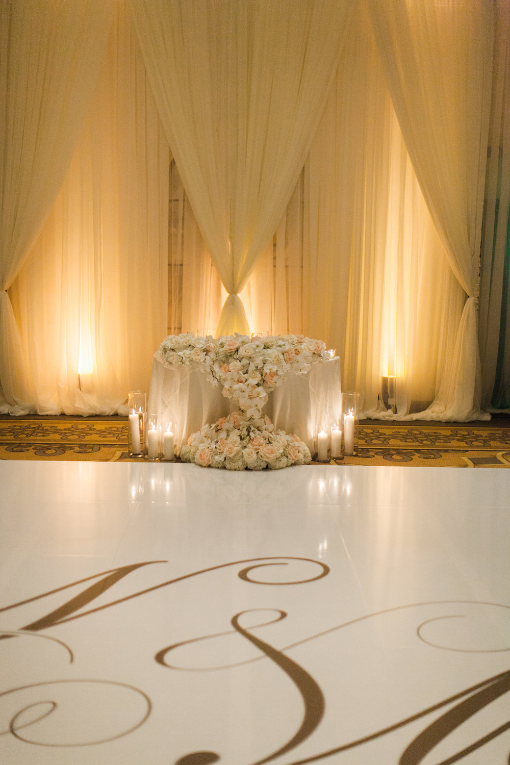 Custom dance floor with the bride and groom's initials mixed with extravagant draping