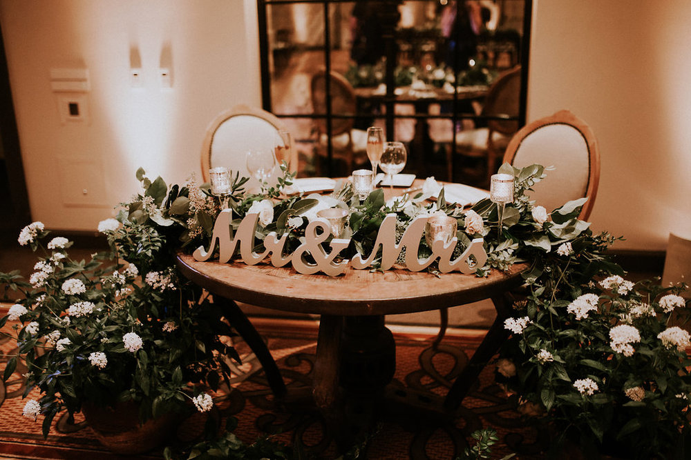 Sweet Blossom Weddings Team moved this garland from the arch to the Sweetheart Table Florist: Native Poppy Photographer: Amy Lynn Photography