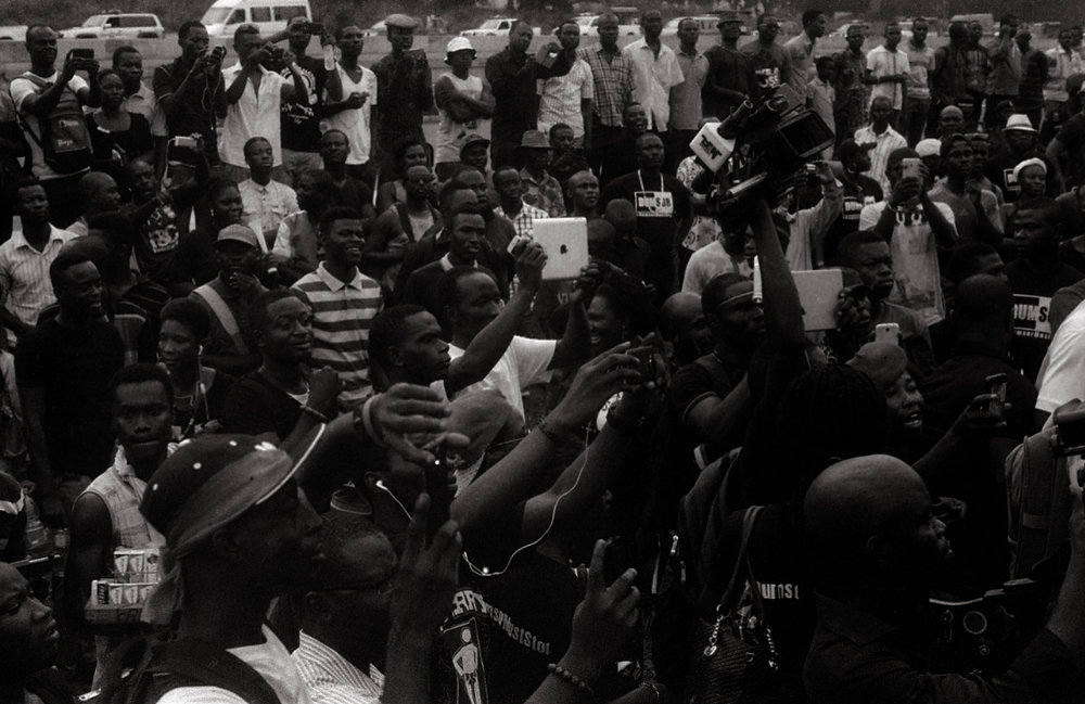 Demonstrators and reporters turn eyes and cameras towards the celebrity organizers of the Dumsor Vigil.