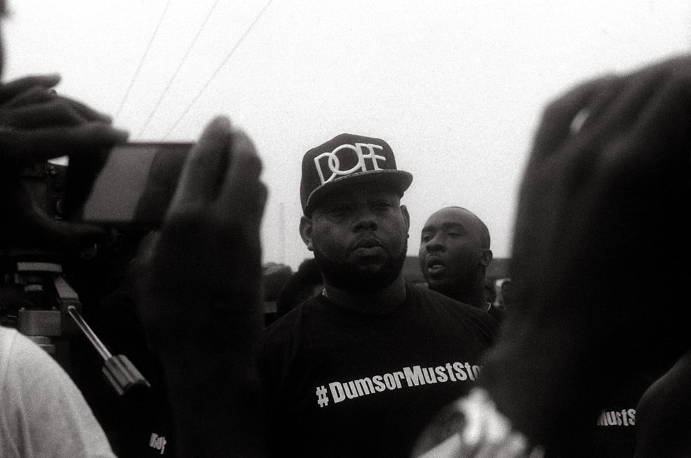 Rapper D-Black wears a t-shirt with the hashtag that helped rally support for the demonstration.