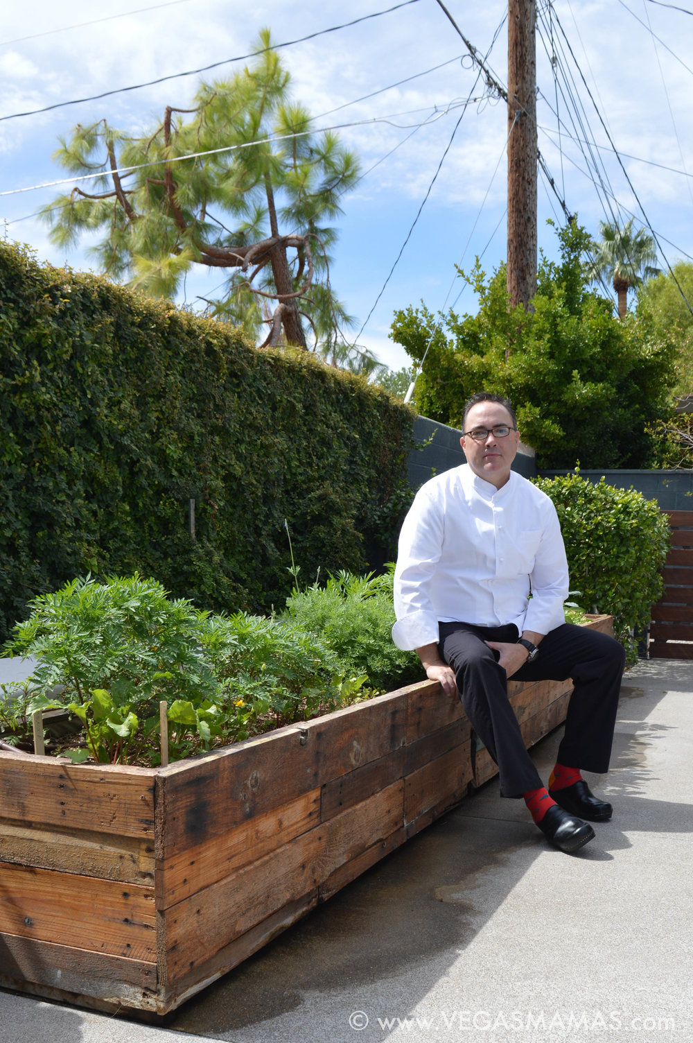 Mark Andelbradt, Michele's husband, seated next to his organic garden