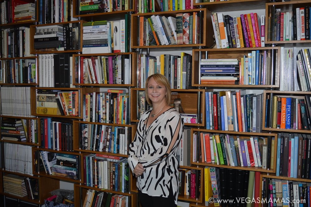 Michele pictured here with her and Mark's in-home library, custom shelves designed by Michele.