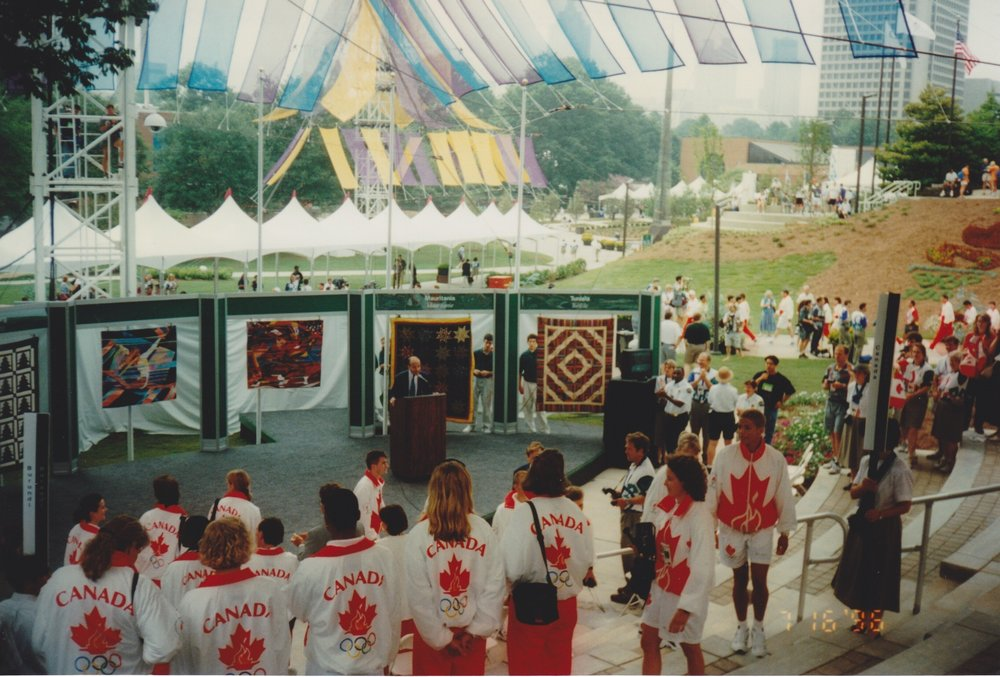 A photo from the personal collection of Mary Ross, during the quilt presentation ceremony she was invited to. Her quilt was given to the flag-bearer of Canada. Quilters were invited to these ceremonies, which was a big deal, because access to the city and the Games was rare. Her quilt is below.