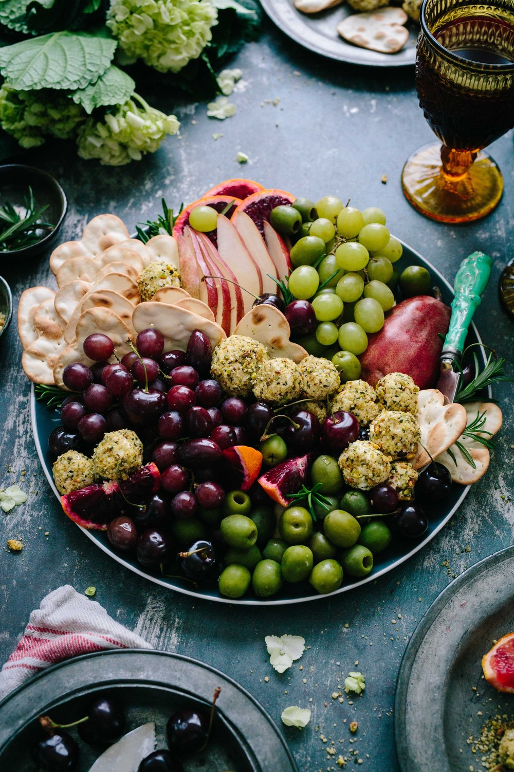 A plate filled with luscious-looking grapes, olives, cheese, and crackers.