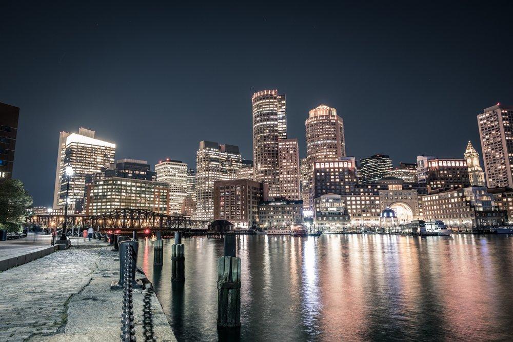 The Boston skyline glitters against the dark night sky.