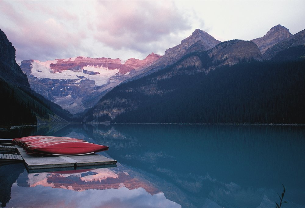 Red kayaks lined up on a dock next to a glassy lake in Banff National Park.