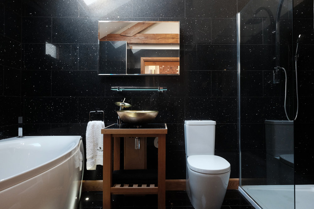 Black sparkly tiled bathroom with spa bath and large walk in shower