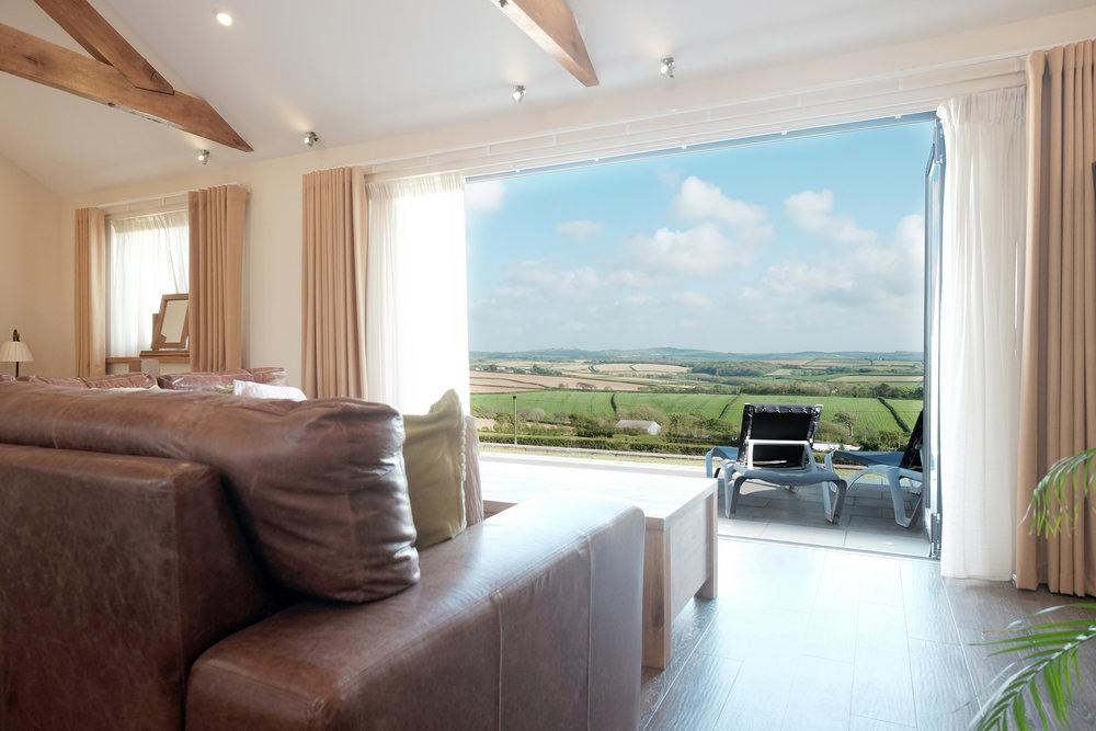 Leather sofa with patio doors open displaying the countryside vistas