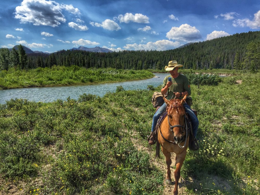 Interviewing cowboy, Clayton Alexander, while riding horses in the Bob Marshall Wilderness of Montana.