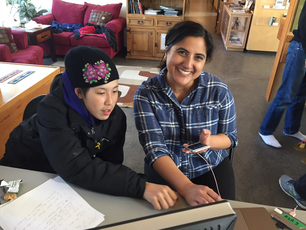 Teacher Sharma (Monica) helps Kayleen get images off of her mom's phone