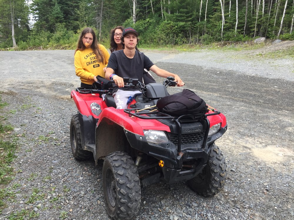 Spencer drives the fourwheeler with Alexa and Emily to the next location