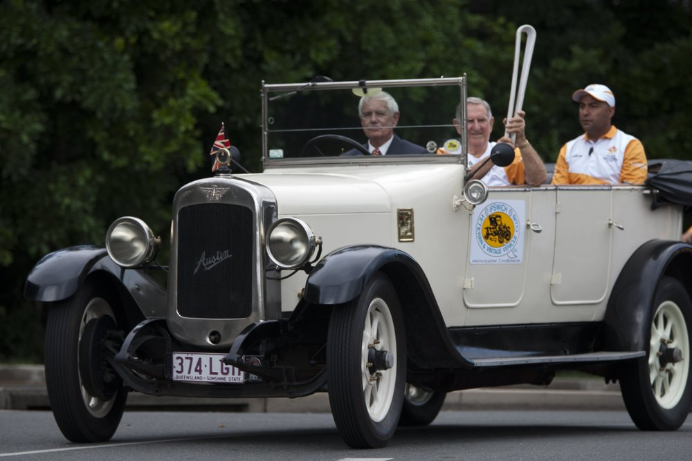 Lyn Stanners driving Tom Edwards with the Queens Baton in his Austin 20 Tourer