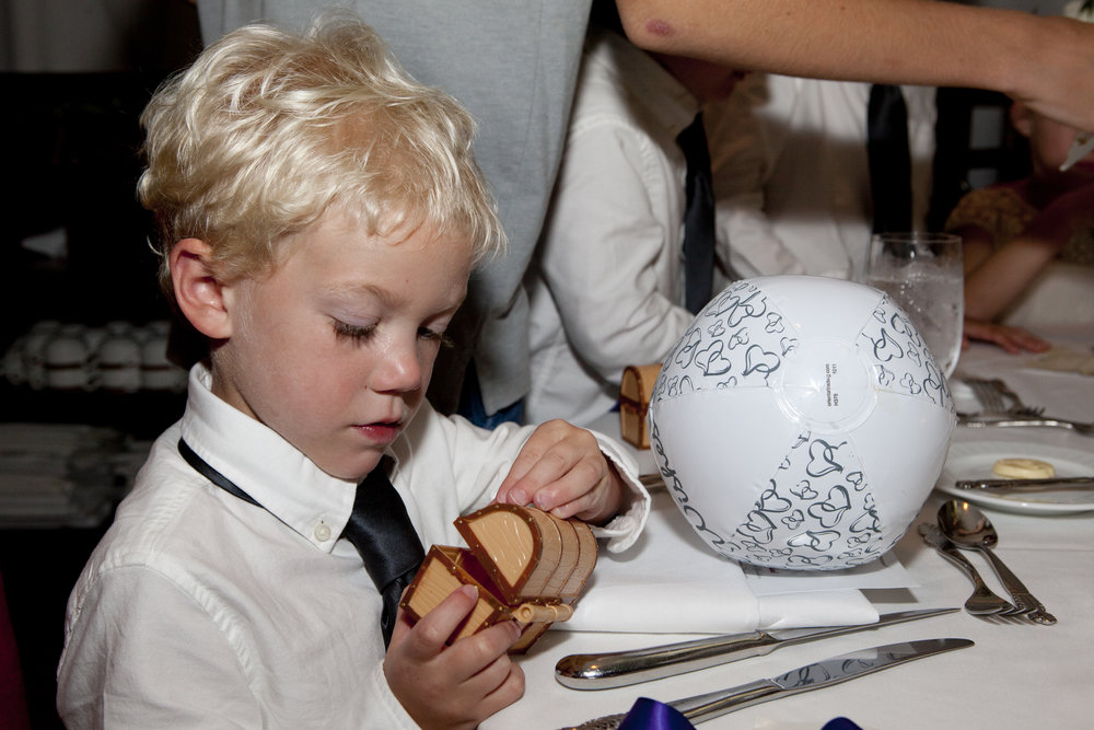 Children's place cards were a key to open up mini treasure box.  Inside each had a part of a treasure map.  they had their own treasure hunt during reception and found buried treasure of indiviual bags of gold wrapped chocolate coins.