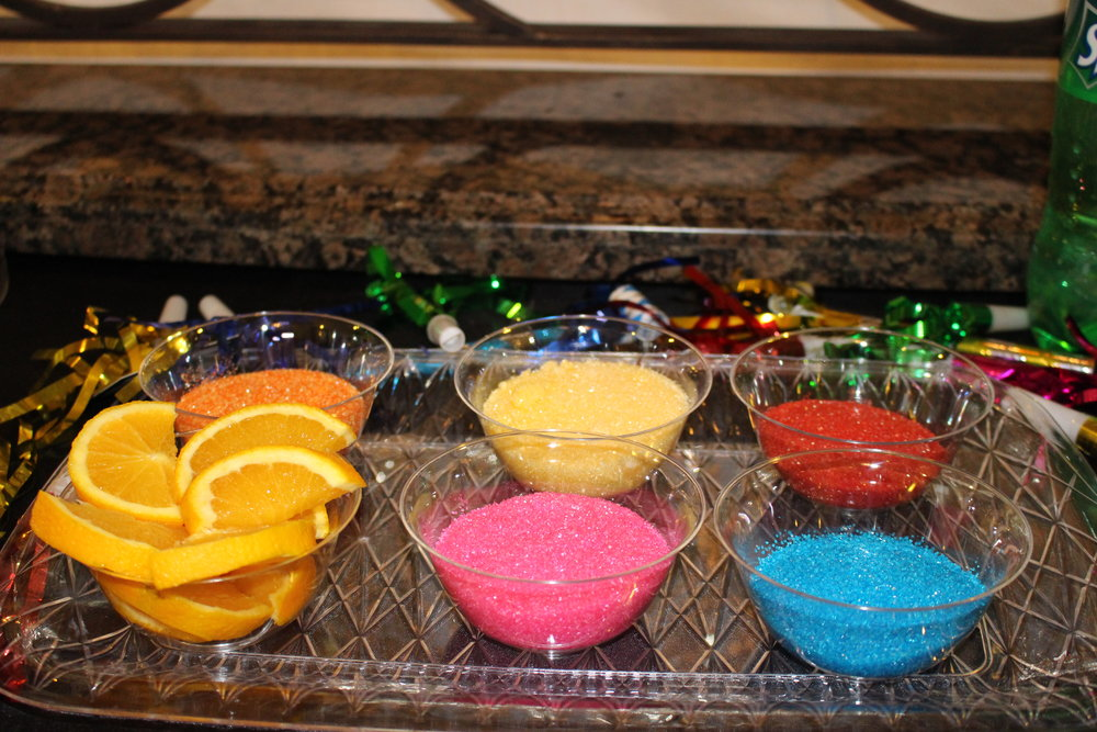 Cut up some oranges into slices with slits in middle and put on tray with small bowls filled with colored sugar from the baking section of local grocery store. The kids can rub the rim of their plastic glass with orange then dip rim into sugar (just like you do with salt for a margarita)