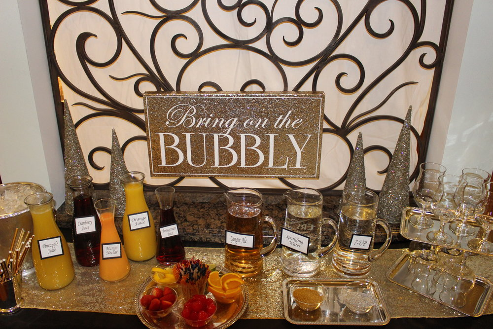 Decorate your Bubbly station with gold and silver. Here we have a gold sequin runner and specialty glasses on silver tray