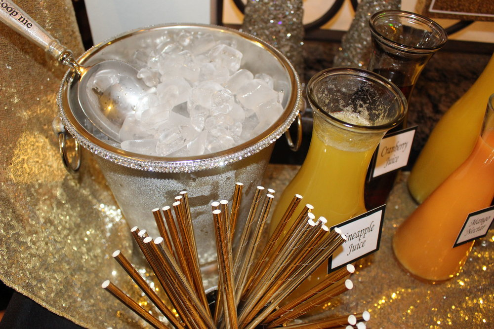 Placing a beautiful silver ice bucket with some gold paper straws always adds glamour to any drink station.