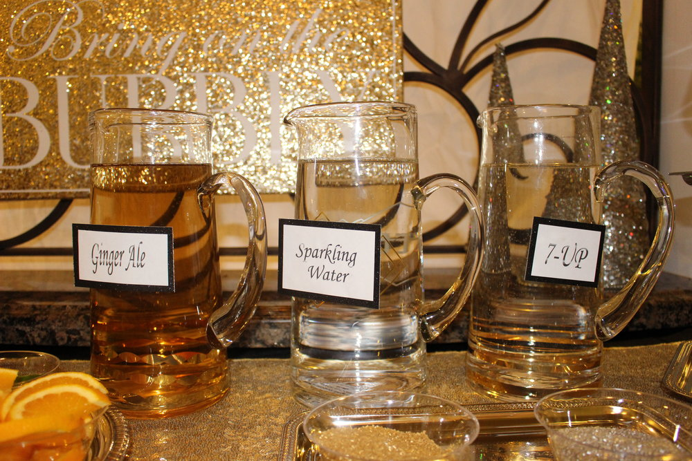 As for the bubbly part of the station, add glass pitchers filled with ginger ale, sparkling water, and 7-up.  We printed out the names on regular white paper, cut them out and glued them to black card stock. We attached the custom signs to pitchers with glue dots .