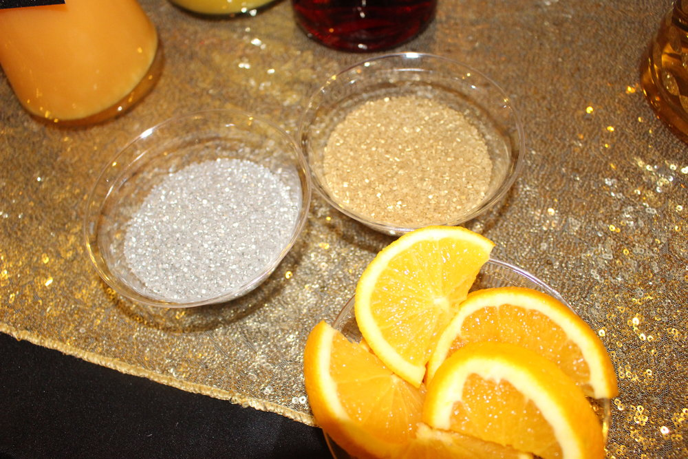 Add orange slices to rim the glasses with gold and silver sugar crystals.  You can find these at Michaels or grocery stores in baking section.