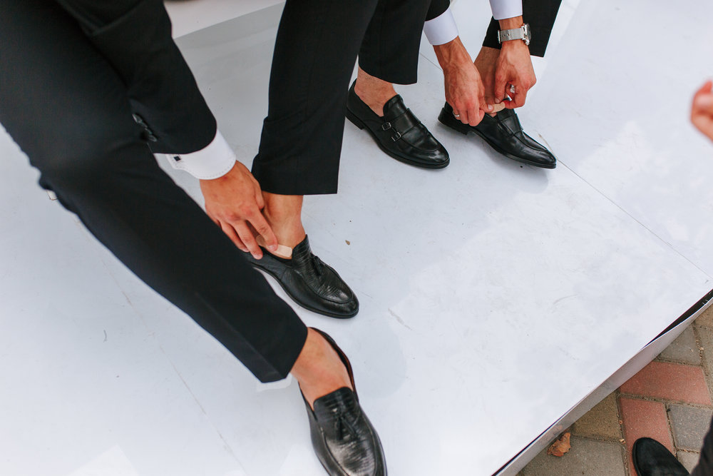 An-elegant-man-puts-on-black,-leather,-formal-shoes-with-plaster.-Wedding-problems-1038188416_5760x3840.jpeg