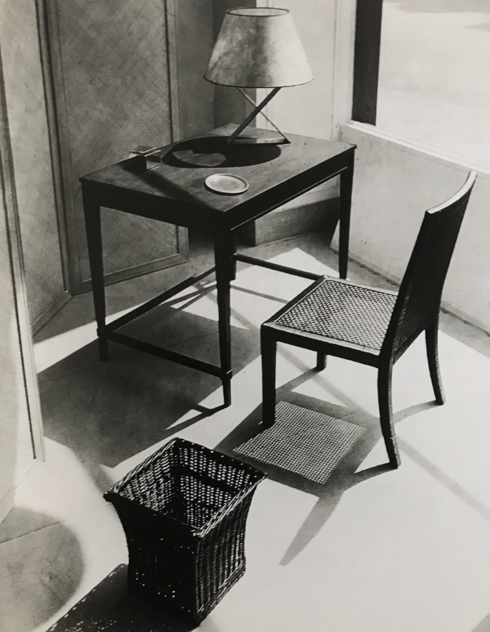 Window display at the Jean-Michel Frank boutique, circa 1935. Dark stained wood lady's desk with plinth legs, chair and basket in woven wicker, the X lamp in metal.