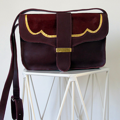 EMILY  _____  Great everyday shoulder bag with adjustable buckle strap  Inside panel pocket and strap front fasten  Burgundy leather with a gold trim detail and a deep red embossed snake suede panel and gun metal buckle  W: 260mm x H: 180mm x D: 60mm  From £220  Choose your colour and materials – please get in touc