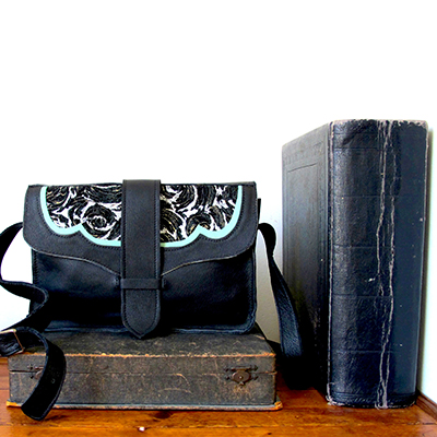 EMILY  _____  Great everyday shoulder bag with adjustable buckle strap  Inside panel pocket and strap front fasten  Black leather with mint green trim and patterned silver metallic suede. Pewter buckle  W: 260mm x H: 180mm x D: 60mm  From £220  Choose your colour and materials – please get in touc