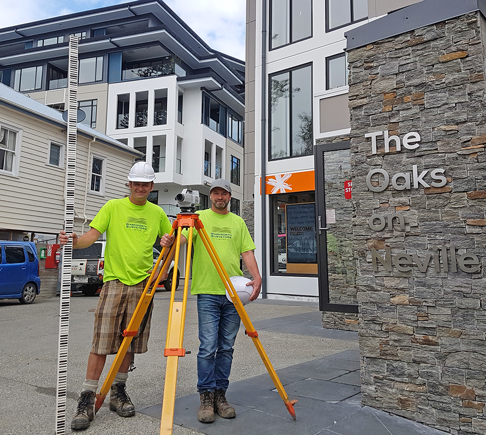 The Oaks on Neville   Our Surveyors Shane Sutton (left) and Simon Knight (right) have been heavily involved in the Oaks on Neville Project for the last few years. They are pictured with our Sokkia SDL30 digital level and bar-coded fibreglass staff. This equipment was used to accurately monitor the height of references pins in the pavement and buildings surrounding the project site. This was to make sure there were no issues while de-watering was being carried out during construction of the underground carpark. This level monitoring commenced in November 2014 and has been repeated at regular intervals until now. Small fluctuations of a few mm in height were observed and in general these mirrored the fluctuations in groundwater levels that the geotechnical engineers were recording at piezometer borehole locations. This enabled management of the volume of water being pumped out of the basement excavation.  Simon and Shane were also responsible for setting out grid positions, reference benchmarks and other specific features during the construction process. This was mainly for the project managers, Kalmar Construction Ltd and for the piling contractor CLL Ltd. There were also numerous requests from both Kalmar and the Oaks on Neville Ltd for urgent topographic surveys to facilitate design changes.  Warkworth Surveyors Ltd gave the Oaks on Neville project top priority in our day to day programming. We made sure there was flexibility in Simon and Shane's weekly tasks to ensure they could be available at short notice to meet construction demands.  We are proud to have been involved in the Oaks on Neville Project.