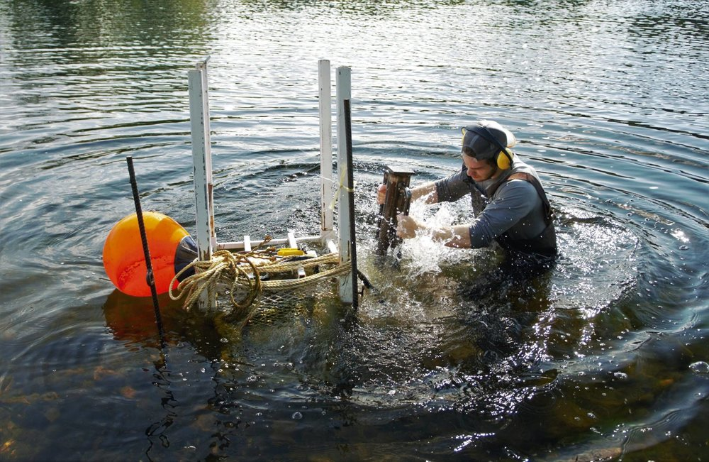 A CAST member pounding rebar in the Miramichi River to secure a sonar camera to allow accurate counting of salmon - Photographed by Jani Helminen