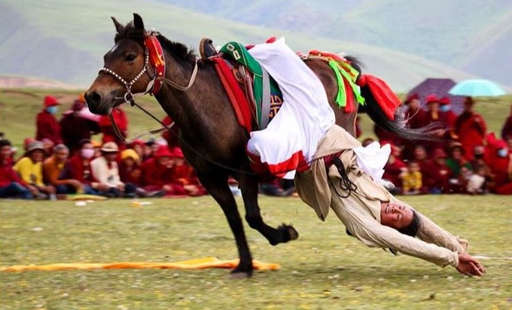 An agile rider shows how he can lower himself to the ground, and then pull himself up again, during the horse racing festival in Tibet.