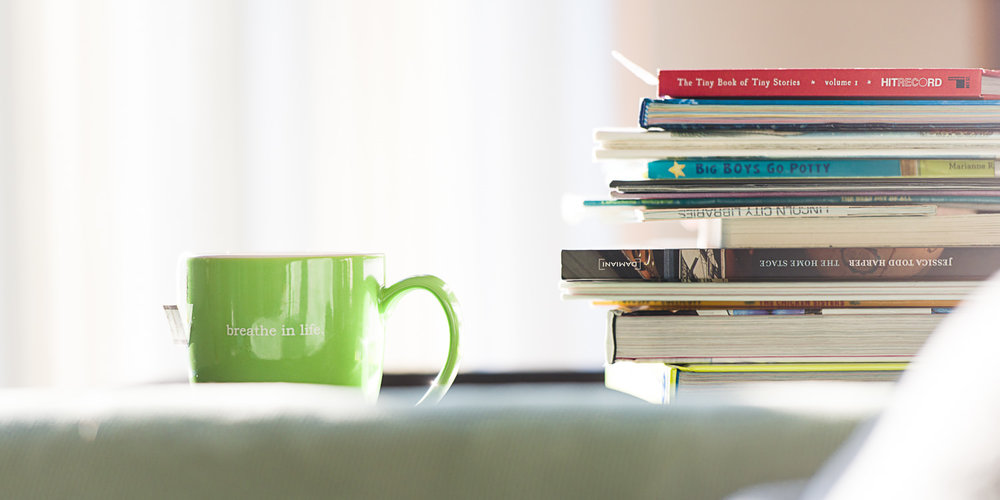 Green cup of tea by a stack of books.