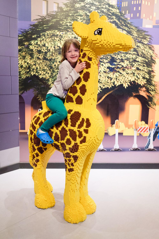 girl on Lego giraffe