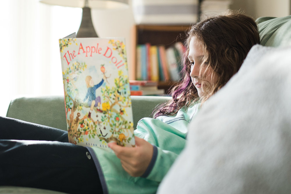 Little girl reading a book on the couch, The Apple Doll