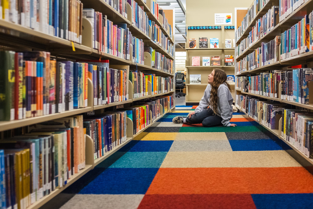 girl gazing at library shelves.jpg