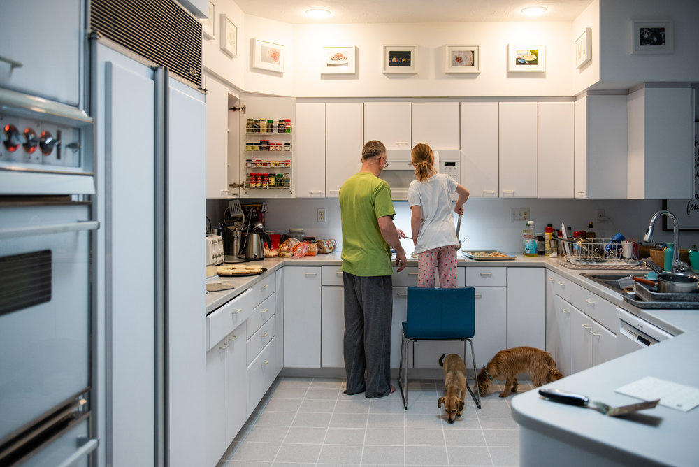 father and daughter cooking together in a white kitchen.jpg