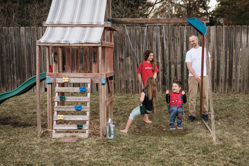 family playing in backyard on swingset in Lincoln Nerbaska.jpg