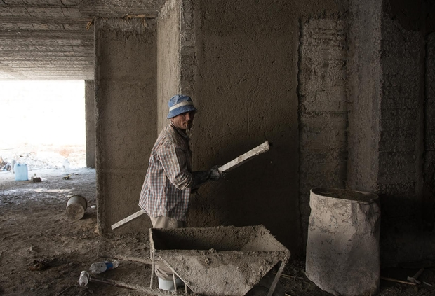 Egyptian construction worker spreads concrete on walls of soon-to-be villa. Photo: Jihad Abaza