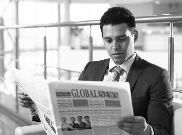 A man is reading a newspaper.