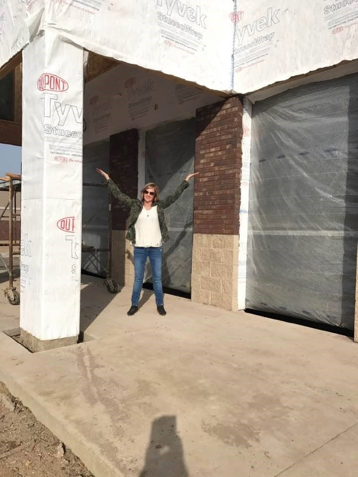 Tamara Dettler, owner of moe's home, standing in front of the future store front