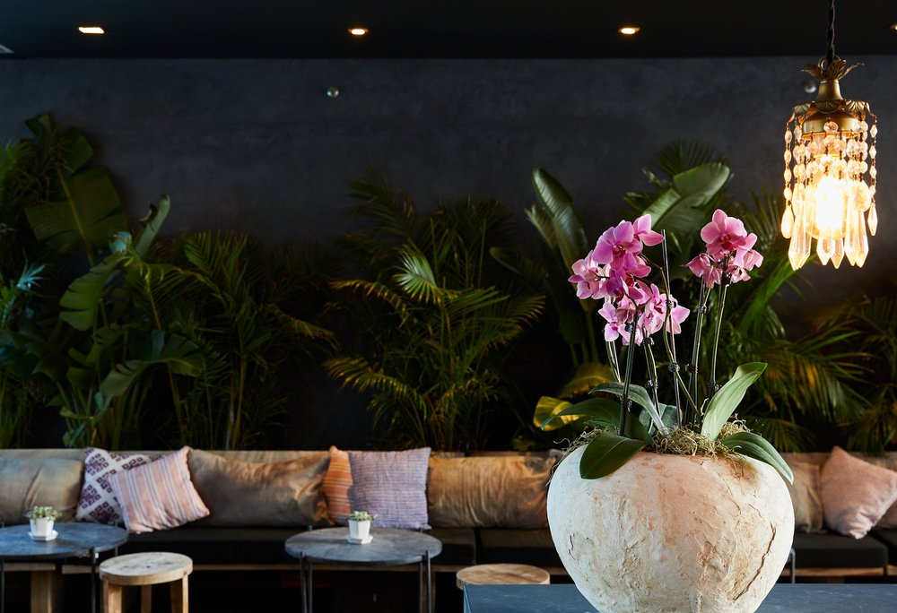 THE JUNGLE BAR WITH WOOD BENCHES, STOOLS AND MARBLE TABLES DESIGNED AND IMPORTED FROM TULUM.